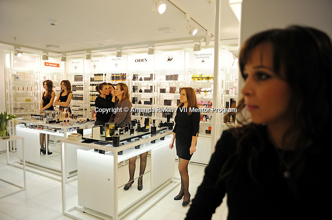 Shop girls stand around while a make-up artist applies make-up to a patron during the grand opening celebration of Emporium's second store at the Port Baku luxury residences in the Azeri capital of Baku, Azerbaijan on October 28, 2011.  Emporium's second store in Baku was designed by Japanese architect Yukio Ishiyama of the Milanese design firm Garde and features over 150 luxury ready-to-wear brands such as Azzedine Alaïa, Marc Jacobs and Stella McCartney; Emporium is widely considered to offer the greatest variety of high-end designer shopping in Baku under one roof.