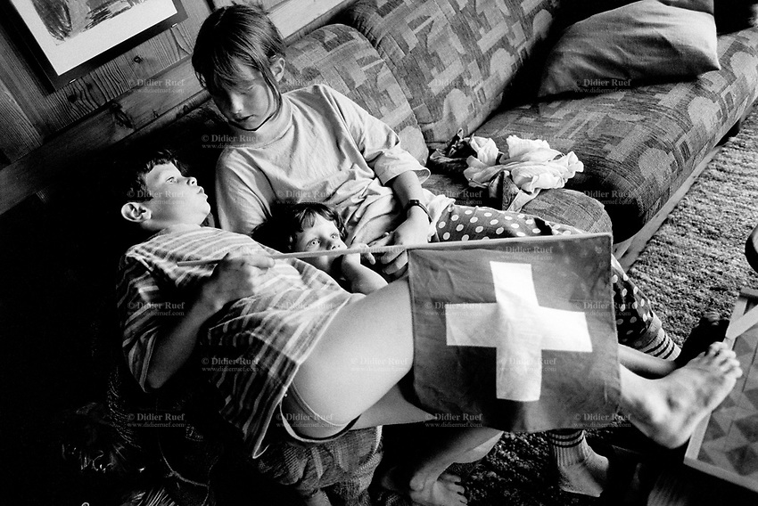 Switzerland. Canton Graubunden. Rumein. Lumnezia valley.  Two boys and a girl seated on a sofa, talk together and play with a swiss flag. Organic farm. Swiss alpine farmers. Alps mountains peasants.  © 1994 Didier Ruef