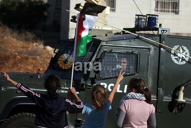 A Palestinian girl holds a Palestinian flag during clashes between Israeli security forces and Palestinian demonstrators at a weekly protest in the West Bank village of Nabi Saleh, near Ramallah November 11, 2011.. Photo by Issam Rimawi