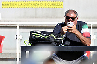 Swimming coach Stefano Morini looks at his smartphone prior to the start of a training session. Some adhesive stripes reading ' respect the safety distance ' have been put on the wall and on the steps to comply the security measures decided by italian swimming federation . <br /> Italian athletes were able to resume training last week after more than 50 days of lockdown due to the coronavirus (covid-19) pandemic <br /> Roma 12-5-2020 Centro Federale di Ostia <br /> Photo Andrea Staccioli / Deepbluemedia / Insidefoto