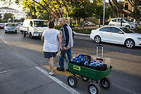 NEWLANDS, SOUTH AFRICA – FEBRUARY 7: A couple pulls a trolley after queuing for free water early in the morning from a well on February 7, 2018 at SAB breweries in Newlands, outside Cape Town, South Africa. The city of Cape Town is experiencing severe water shortage and water restrictions are in place. The big users of water are not the poor in the townships, but the wealthy people in the suburbs who have pools and gardens, and who are now forced to save on water. (Photo by Per-Anders Pettersson)