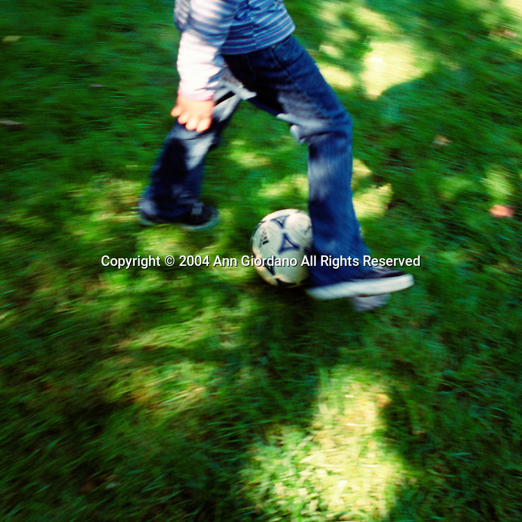 Child from waist down with soccer ball on grass