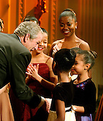 Washington, D.C. - February 6, 2006 -- United States President George W. Bush is surrounded by young dancers from the Dance Theatre of Harlem following their performance the the East Room of the White House in Washington, D.C. on February 6, 2006.  <br /> Credit: Ron Sachs / CNP