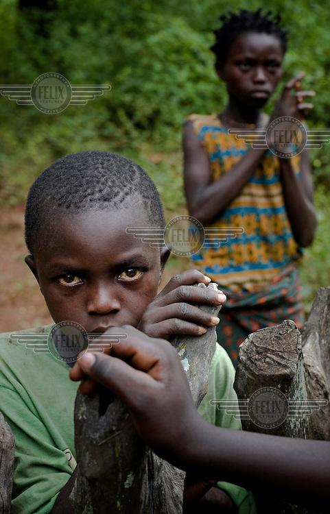 Two children wait near a village.