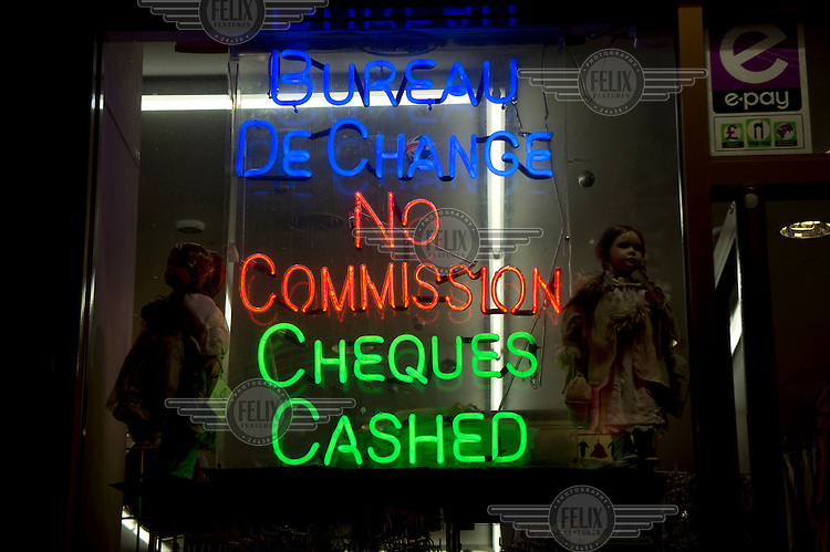 A neon sign in the window of a shop advertising financial services, in Paddington, West London.