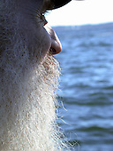 The old man looks out at the sea.  His long gray beard is shining with the sun shining thru it.