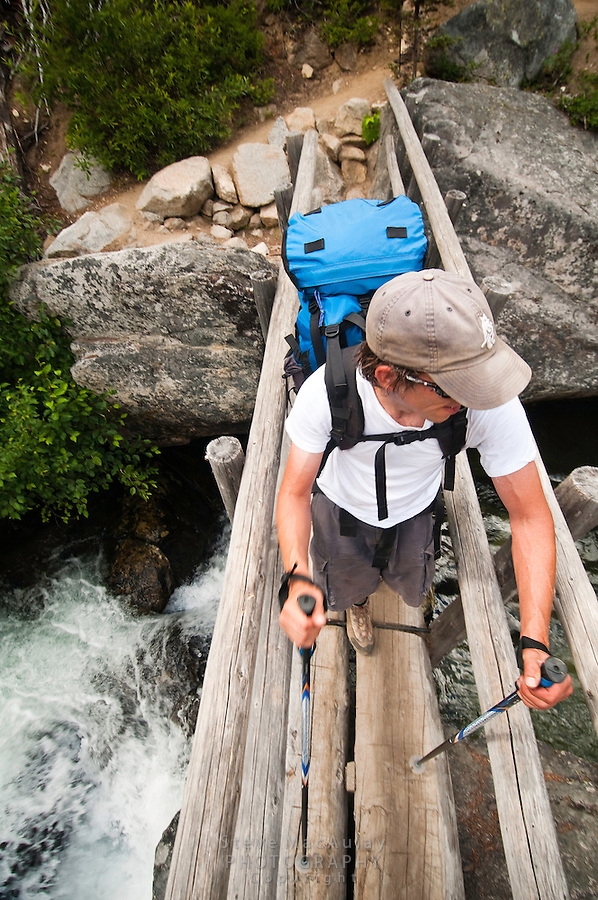 Backpacker crossing log bridge over river, en-route to the Enchantments, Alpine Lakes Wilderness, WA.