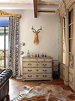 The walls of the living room and entrance have been painted with tinted lime wash, layered to create an aged effect. A collection of blue glass is displayed on a chest of drawers with a distressed painted finish.