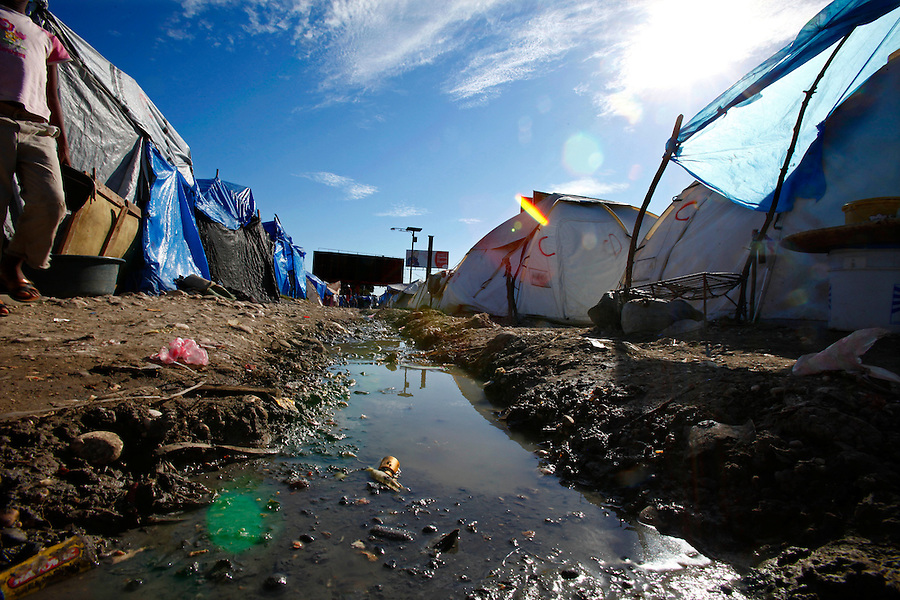 Nov 11, 2010 - Port-au-Prince, Haiti.A stagnant drainage ditch filled with water, garbage and possible human waste runs through a tent city in Port-au-Prince, Haiti on Thursday, November 11, 2010 as fears of a Cholera outbreak spread through the area just days after cases of the infection were confirmed in Haiti's capital. Officials from the Pan American Health Organization warn that Haiti's cholera epidemic, spread primarily through consuming infected water and food, is likely to grow much larger in the wake of Hurricane Tomas.  (Credit Image: Brian Blanco/ZUMA Press)