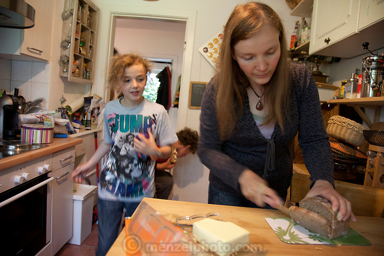 Astrid Hollmann cutting bread in her kitchen for her sons' snacks after school in Hamburg, Germany. The family was photographed for the Hungry Planet: What I Eat project with a week's worth of food. Model Released.