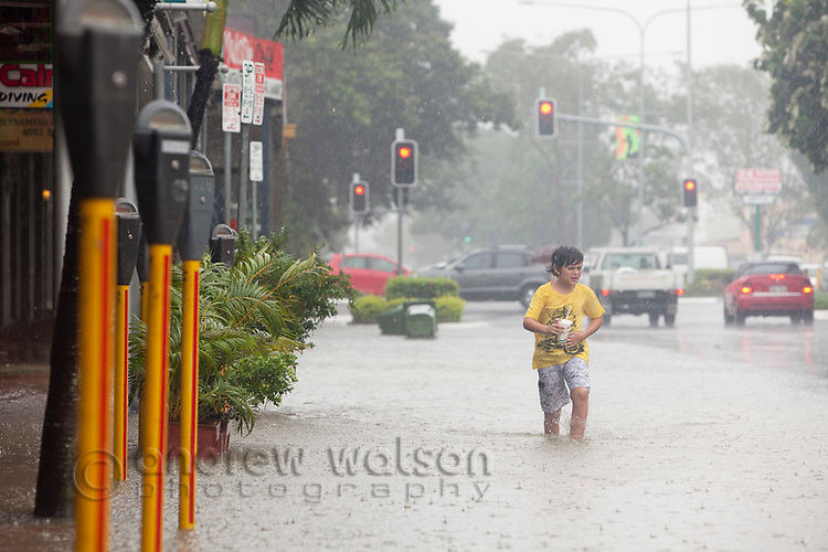 Boy playing in street flooded due to torrential rain and king tides.  Cairns, Queensland, Australia