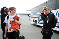 STANFORD, CA--Toni Kokenis watches teammate Joslyn Tinkle check her hair on her iPhone while waiting on the tarmac before traveling to Denver, CO for the 2012 NCAA Women's Final Four.