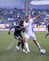 New England Revolution forward Sainey Nyassi (14) tackles San Jose Earthquakes defender Ramiro Corrales (12).  The New England Revolution and San Jose Earthquakes play to a scoreless draw at Gillette Stadium on May 15, 2010.