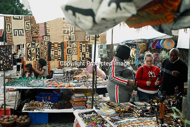 African immigrant women work on their hair as they sell African goods at the Green Market square market.  Photo by: Per-Anders Pettersson/Getty Images for Smithsonian Magazine.
