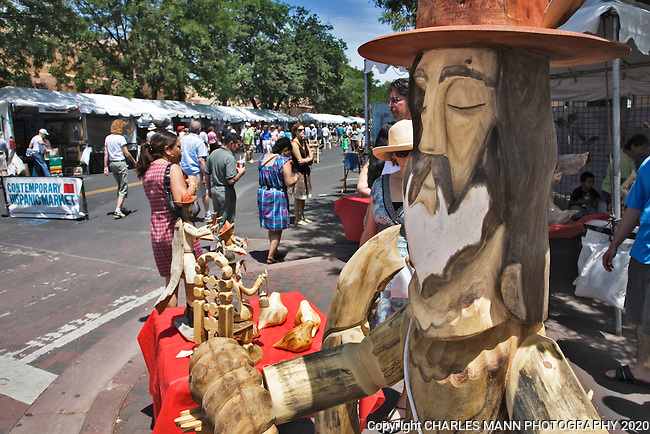 A wooden carving by Pete Ortega frames a scene at the 2009 Spanish Market, an event held each July on the plaza at Santa Fe, New Mexico