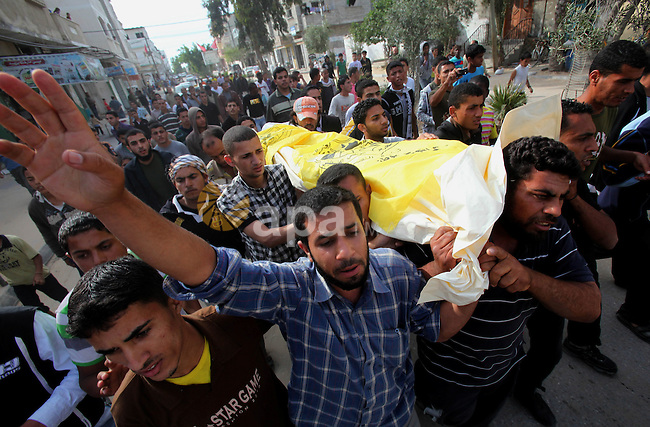 Palestinians carry the body of Ibraheem Farajallah during his funeral at the Nuseirat refugee camp in the central Gaza Strip May 21, 2011. Israeli troops shot dead a Palestinian spotted approaching its boundary fence with Gaza. Gaza hospital officials retrieved the body of a 19-year-old man who was not claimed as a member by any Palestinian militant groups, leaving the possibility that he had been planning to cross from impoverished Gaza into Israel to search for work. The army said he was suspected of trying to plant a bomb against Israeli patrols. Photo by Ali Jadallah
