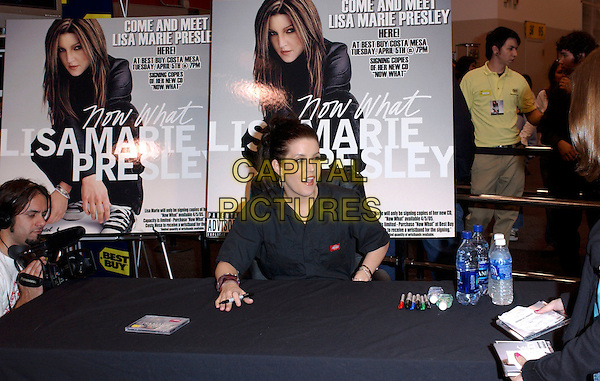 "LISA MARIE PRESLEY.Signs copies of her new CD release, ""Now What"" at Best Buy in Costa Mesa, Los Angeles, California, USA,.April 5th 2005..half length record signing LA silver hoop earrings.Ref: DVS.www.capitalpictures.com.sales@capitalpictures.com.©Debbie VanStory/Capital Pictures"