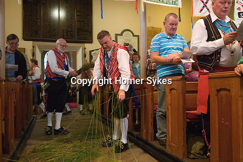 Uppermill, Saddleworth, Yorkshire, UK. St Chad's church, rushes being strewn on the floor of the church during the church service by the Saddleworth Morris men.