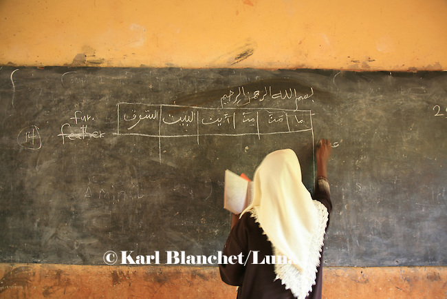 A  teacher from the Islamic school in Sunyani, Ghana, writing arabic sentences on the black board. In Ghana, coranic schools were transformed into islamic schools. Pupils learn the mainstream curriculum and have additional courses in arabic and islam.
