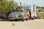 A little dog runs by an artcar pickup truck hitched to 1960s aluminum sided travel trailer at the Slabs near Niland, Calif.