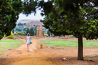 Tourist visiting Valley of the Temples (Valle dei Templi), Temple of Castor and Pollux, Agrigento, Sicily, Italy, Europe. This is a photo of a tourist visiting the ruins of The Temple of Castor and Pollux at The Valley of the Temples (Valle dei Templi).