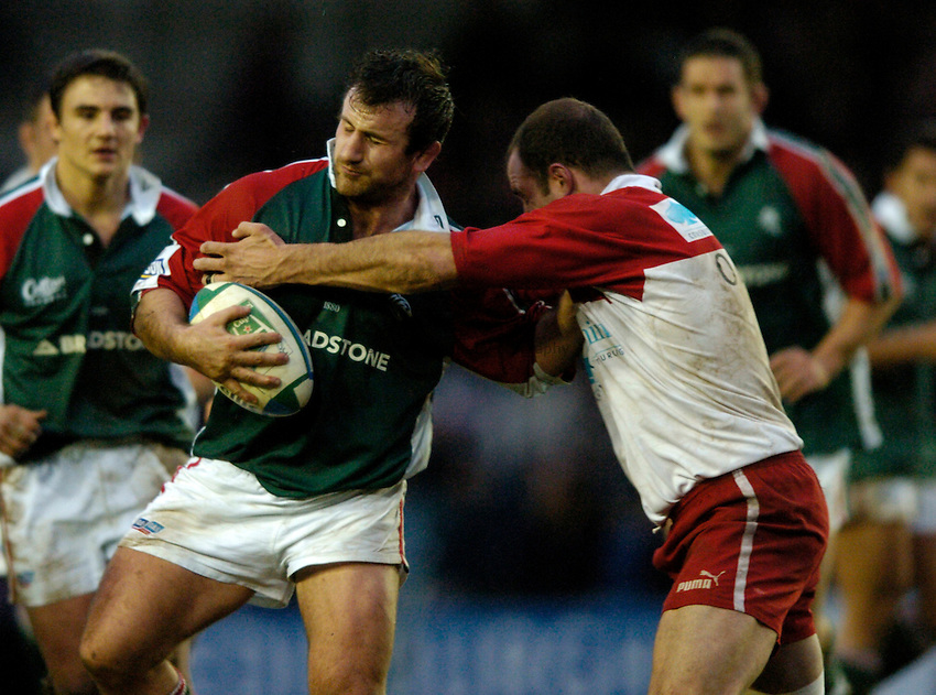 Photo: Richard Lane..Leicester Tigers v Biarritz Olympique. Heineken Cup. 09/01/2005..George Chuter is tackled by Olivier Olibeau.