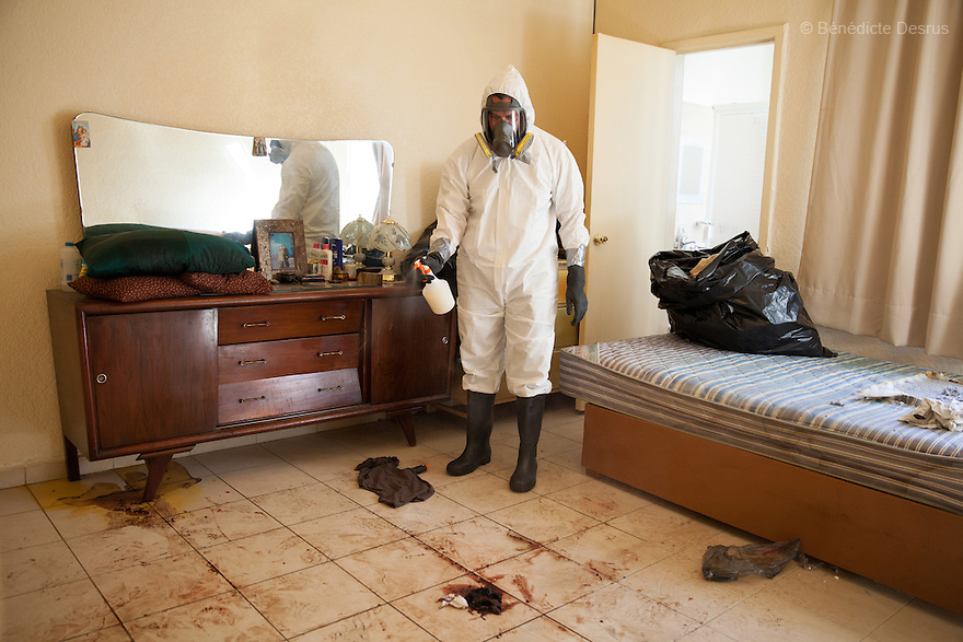 """Donovan using one of the 370 customized formulas which he has devised to carry out a forensic cleaning in Mexico City, Mexico on January 14, 2016. The decomposed body of a man in his 50s was found on the floor of his mother's bedroom, days after he had died of an intestinal obstruction. Because of her physical disability, the mother of the deceased – who had been her caregiver – was unable to move enough to make an emergency call. As a consequence, she was trapped in the room for three days with the body of her son – and without food or water - before help arrived. Donovan Tavera, 43, is the director of """"Limpieza Forense México"""", the country's first and so far the only government-accredited forensic cleaning company. Since 2000, Tavera, a self-taught forensic technician, and his family have offered services to clean up homicides, unattended death, suicides, the homes of compulsive hoarders and houses destroyed by fire or flooding. Despite rising violence that has left 70,000 people dead and 23,000 disappeared since 2006, Mexico has only one certified forensic cleaner. As a consequence, the biological hazards associated with crime scenes are going unchecked all around the country. Photo by Bénédicte Desrus"""