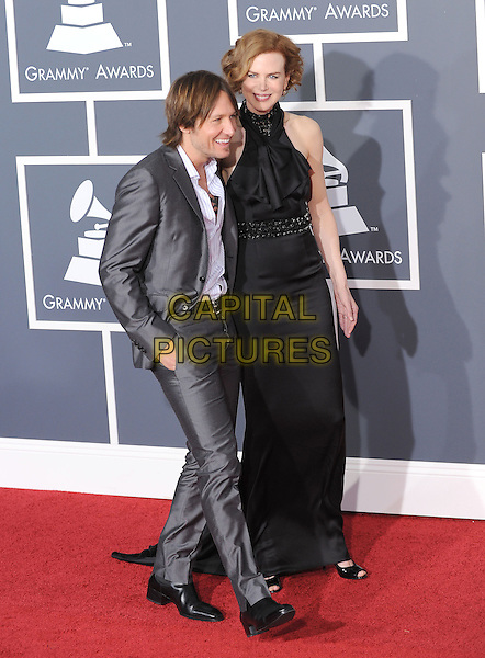 KEITH URBAN & NICOLE KIDMAN.Arrivals at the 52nd Annual GRAMMY Awards held at The Staples Center in Los Angeles, California, USA..January 31st, 2010.grammys full length married husband wife grey gray silver suit holding hands black maxi dress sleeveless halterneck white shirt tall short hand in pockets profile .CAP/RKE/DVS.©DVS/RockinExposures/Capital Pictures
