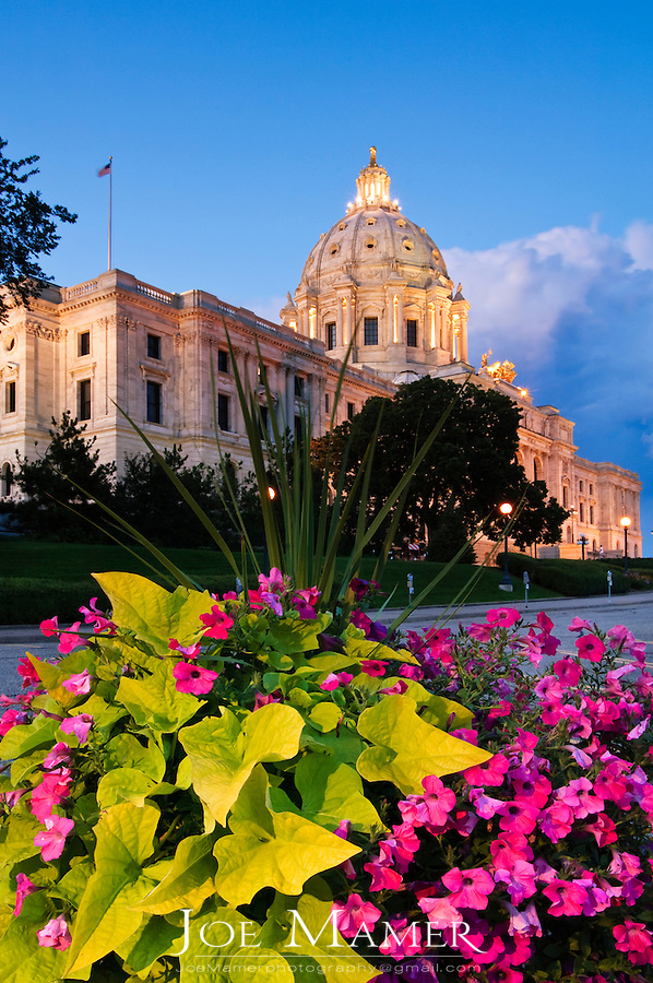 Floral display in front of the Minnesota State capitol building. The building was designed by Cass Gilbert. The unsupported dome is the second largest in the world, after Saint Peter's. Work began in on the capitol in 1896, and construction was completed in 1905. It is the third building to serve this purpose: the first capitol was destroyed by fire in 1881, and the second was completed in 1883, but was considered to be too small almost immediately...
