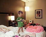 After having had most of her make up done by a professional, Evie, 2, is waiting in the hotel room for her mother to come and dress her up for the Tu Tu Glitz on Tour beauty pageant. Atlanta, Georgia.