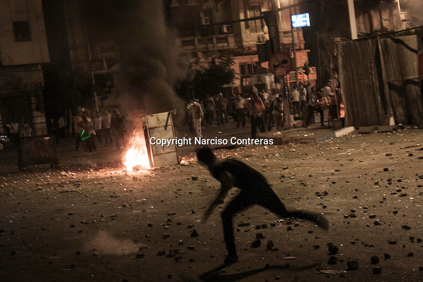 In this Monday, Jul. 15, 2013 photo, an anti- Morsi protester throws stones to the supporters of the ousted president Mohammed Morsi as clashed erupted between them during night in the nearby streets of Ramses bridge in Cairo, Egypt. (Photo/Narciso Contreras).