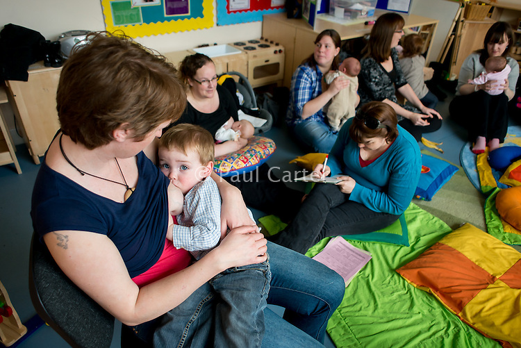A mother breastfeeding her toddler at a drop-in breastfeeding support centre.<br /> <br /> Image from the &quot;We Do It In Public&quot; documentary photography project collection: <br />  www.breastfeedinginpublic.co.uk<br /> <br /> Dorset, England, UK<br /> 17/04/2013