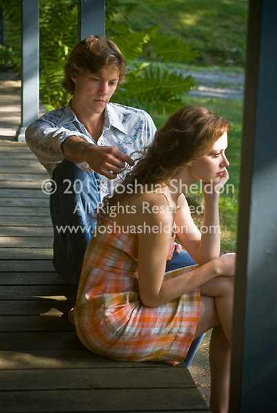 Young couple seated together on porch, he touching her hair