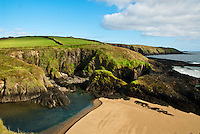 South Ireland Irish coast with sea, hidden swimming cove near Dunworley Beach, blue skies, clouds, sand, green fields, ocean, cove, County Cork, Celtic Sea
