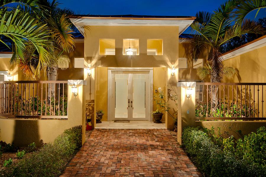 View of front door of residence with glass door.