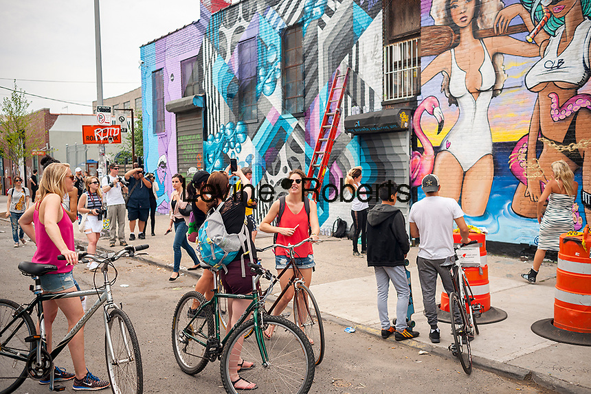 "Thousands pour into Bushwick, Brooklyn in New York for the annual Bushwick Collective Block Party on Saturday, June 4, 2016. Music and partying brought some but the real attraction was the new murals  by ""graffiti"" artists that decorate the walls of the buildings that the collective uses.  (© Richard B. Levine)"
