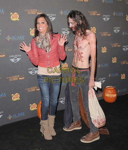 Melissa Rycroft-Strickland & zombie.at 3rd Annual Los Angeles Haunted Hayrideheld at Griffith Park, Old Zoo, Los Angeles, California, USA..9th October 2011  .full length jacket jeans denim beige boots pink leather brown white grey gray print scarf hands funny scared topless chest side profile beard facial hair costume.CAP/RKE/DVS.©DVS/RockinExposures/Capital Pictures