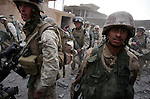 US Marines and Iraqi soldiers with Golf Co. 2nd Battalion 1st Marines make their way through a breach in a wall made by combat engineers to avoid walking through open streets and exposing themselves to sniper fire or opening gateways and doors which could be booby-trapped or conceal waiting insurgents during the third day of Operation Steel Curtain, an operation to clear Husaybah (a city on the Iraq-Syrian border) of insurgents on Mon. Nov. 7, 2005.