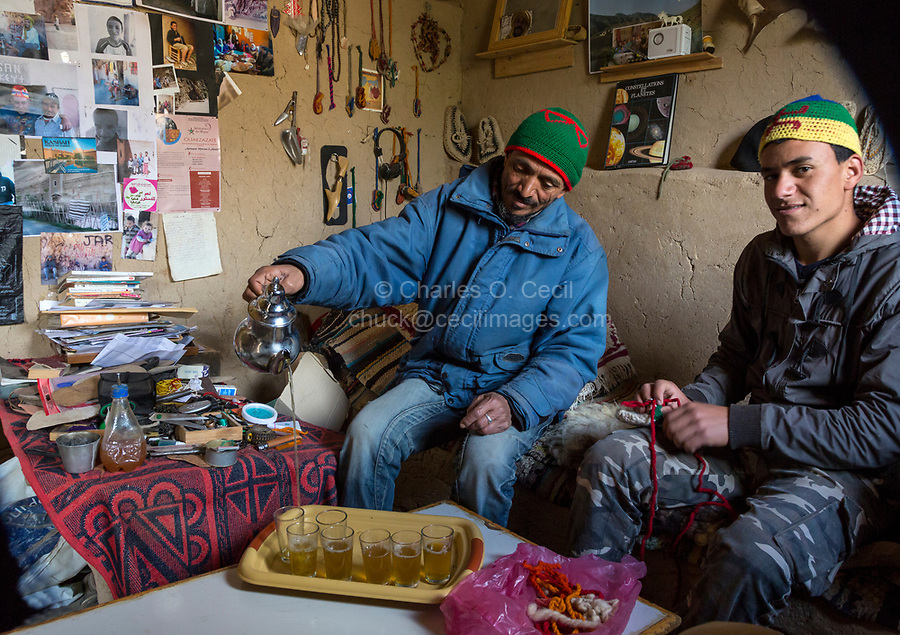 Dades Gorge, Morocco.  Middle-aged Berber Man and 19-year-old Son Pouring Tea for Guests.