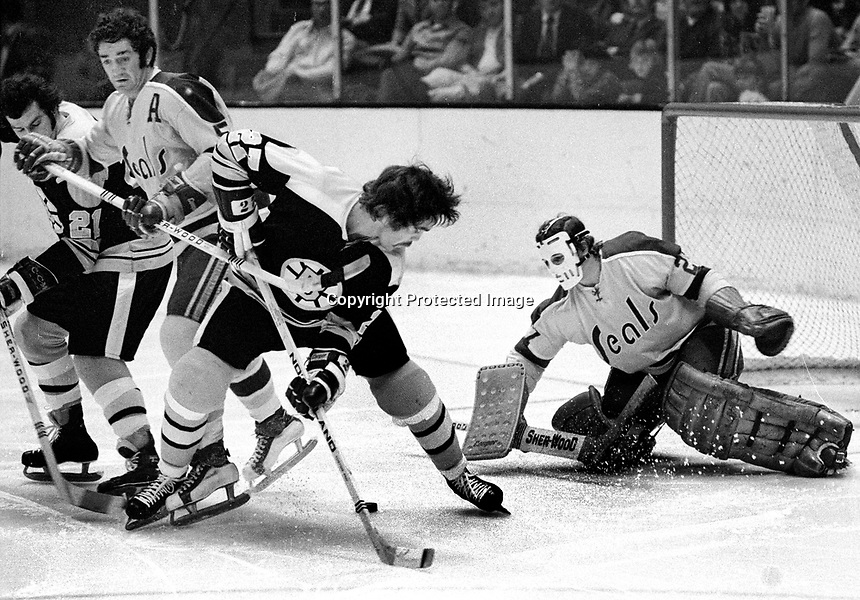 Boston Bruins Dave Hynes in on Seals Gilles Meloche.<br />(1973 photo/Ron Riesterer)