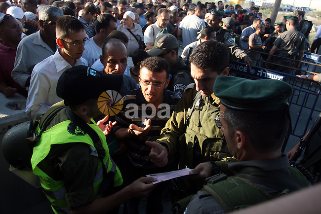 Palestinian men show their ID cards to an Israeli border policeman as they wait to cross through an military checkpoint on their way to pray at the al-Aqsa Mosque in Jerusalem, on the third Friday of the Muslim holy month of Ramadan near the West Bank city of Ramallah on Aug. 3, 2012. Photo by Issam Rimawi