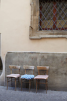 A trio of wooden chairs each with a makeshift cushion is lined up against the wall of a house on a cobbled street of Foligno