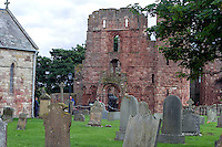 Lindisfarne Priory graveyard with ruins in background Holy Island village