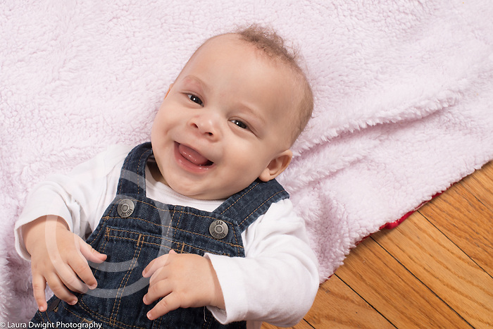 6 month old baby boy on back closeup smiling happy