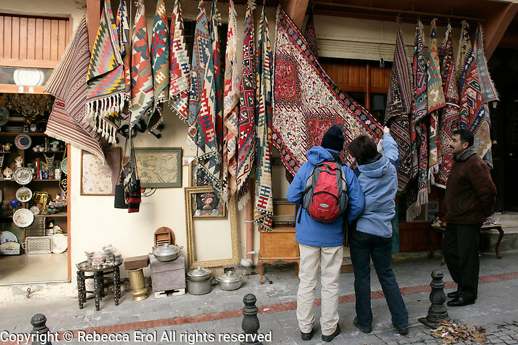Tourists looking at carpets in the antiques market area of Kadikoy in Istanbul, Turkey