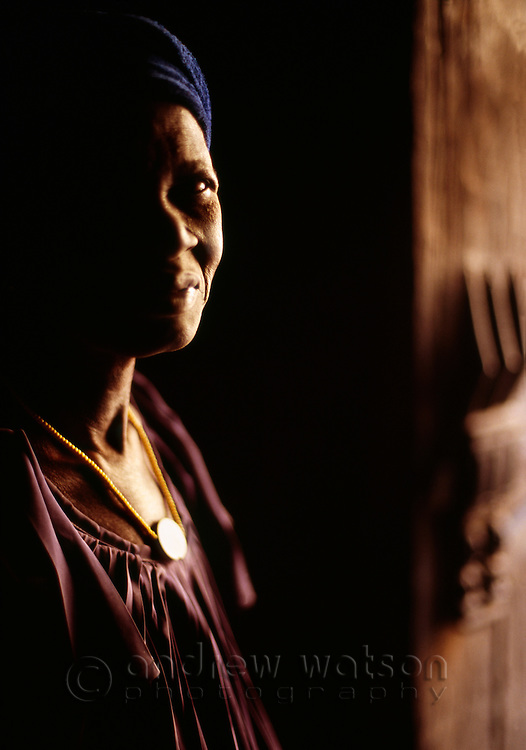A Dogon woman stands in the doorway of a traditional adobe house in the village of Ende, Pays Dogon, MALI