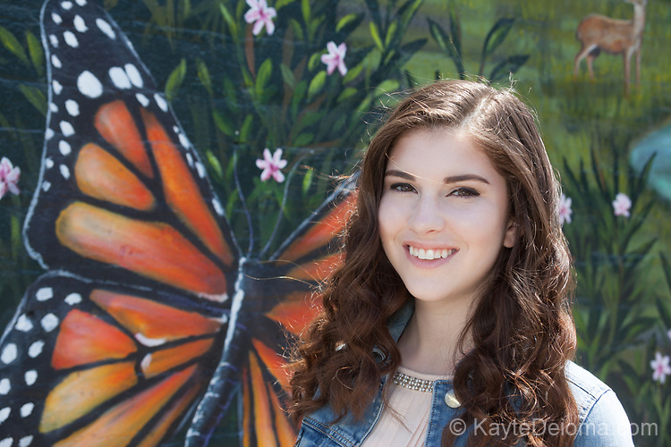 Portrait of a pretty teenage girl with dark brown hair in front of a butterfly mural