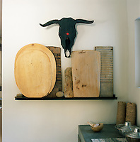 A collection of wooden boards are displayed on a shelf beneath a painted animal skull.