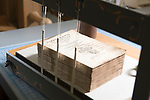 A rare book is prepared for resewing on alum-tawwed leather tongs. The book is part of the collection of Preservation Services in the University of Washington Libraries. Photo by Daniel Berman for UW Columns