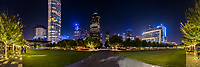 Klyde Warren Park Night Pano -  Klyde Warren Park at night  with the Dallas Skyline and the trees lighted in the park.  The Klyde Warren Park is 5.2 acrea park in the heart of the art district which sit over the Woodall Rodgers freeway in the downtown area of the city.  In the cityscape you can see some of the towering skyscrapers like the Chase Tower, Hunt oil building along with the Dallas Museum of Art.  The park has a children play area, a dog park, open area for play or yoga, a restaurant, and on the days we were there they had many food trucks lined along the street to catch a quick bite to eat. Dallas skyline stock photos.